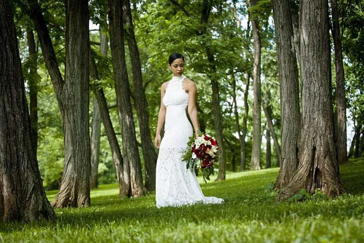 Bride portrait in a grove of trees looking at her bouquet