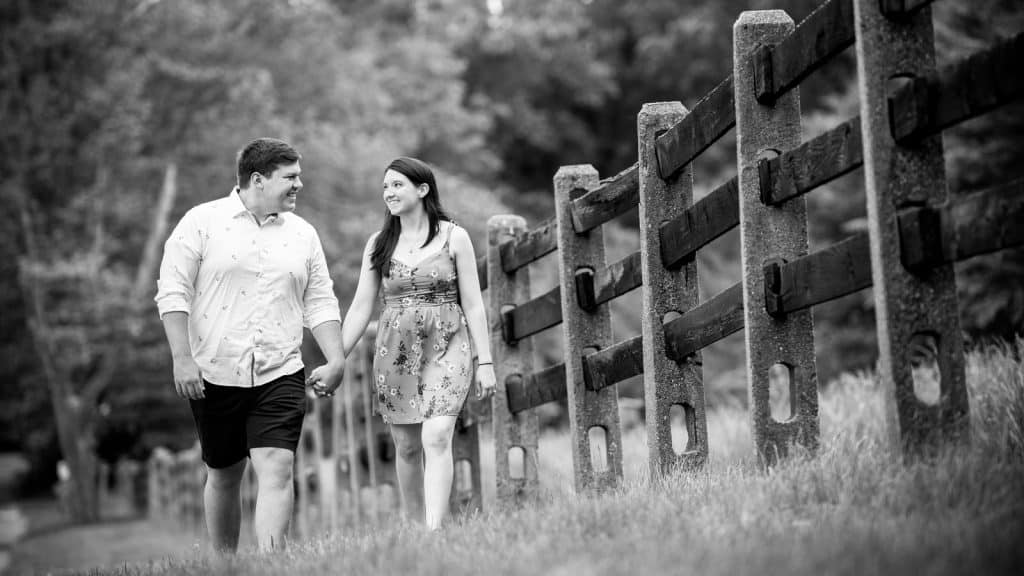 engagement session walking near a wooden fence