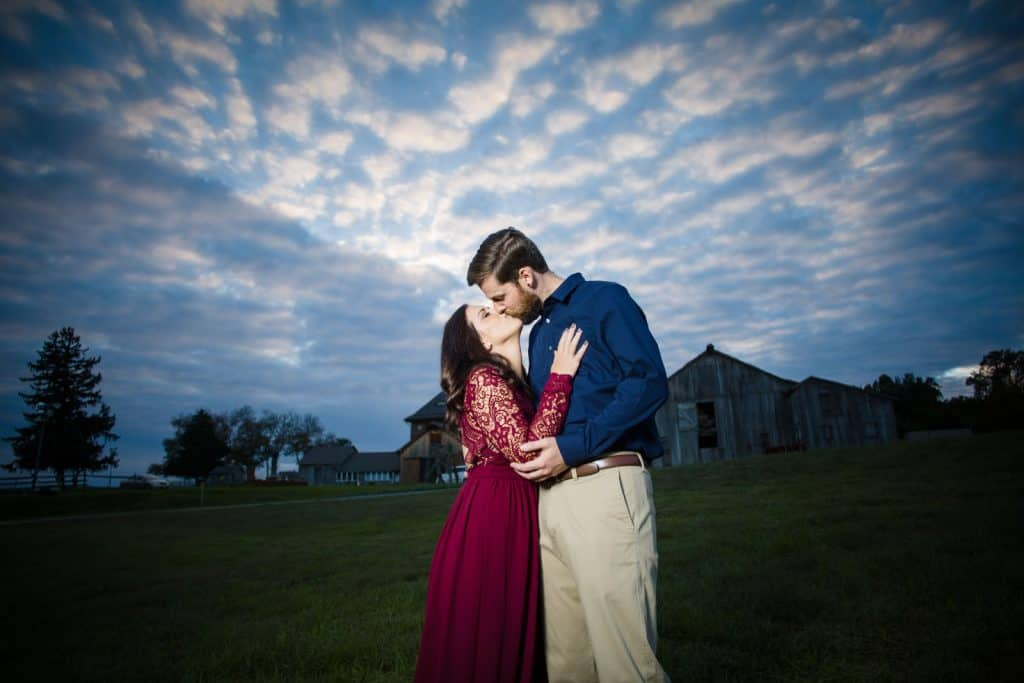 engagement session kissing with farm in the background