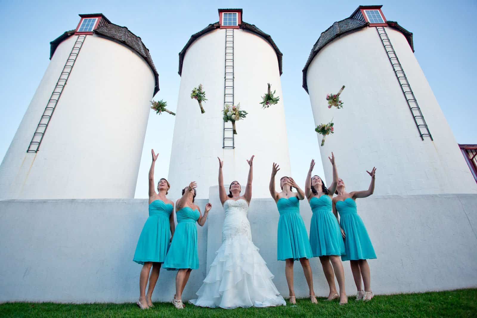 Bridesmaid group throwing flowers in the air at Normandy Farm