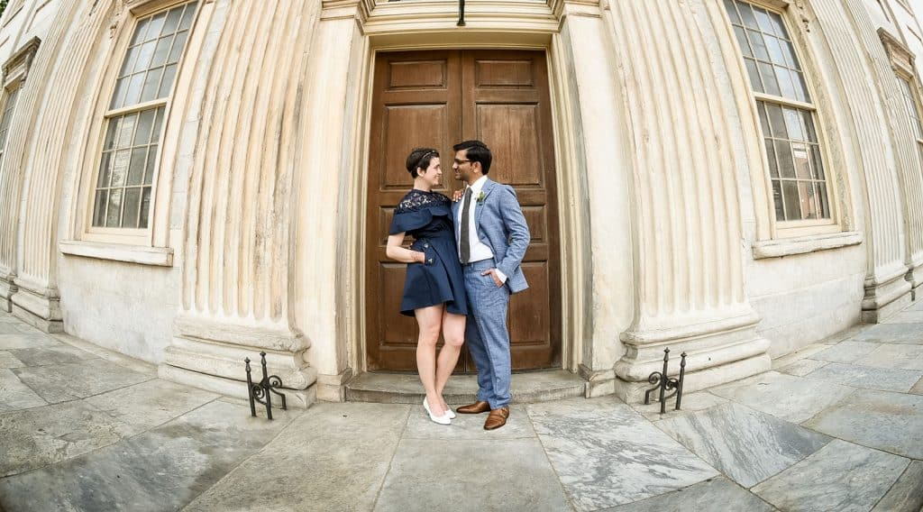 couple in front of wooden door in Philadelphia, PA