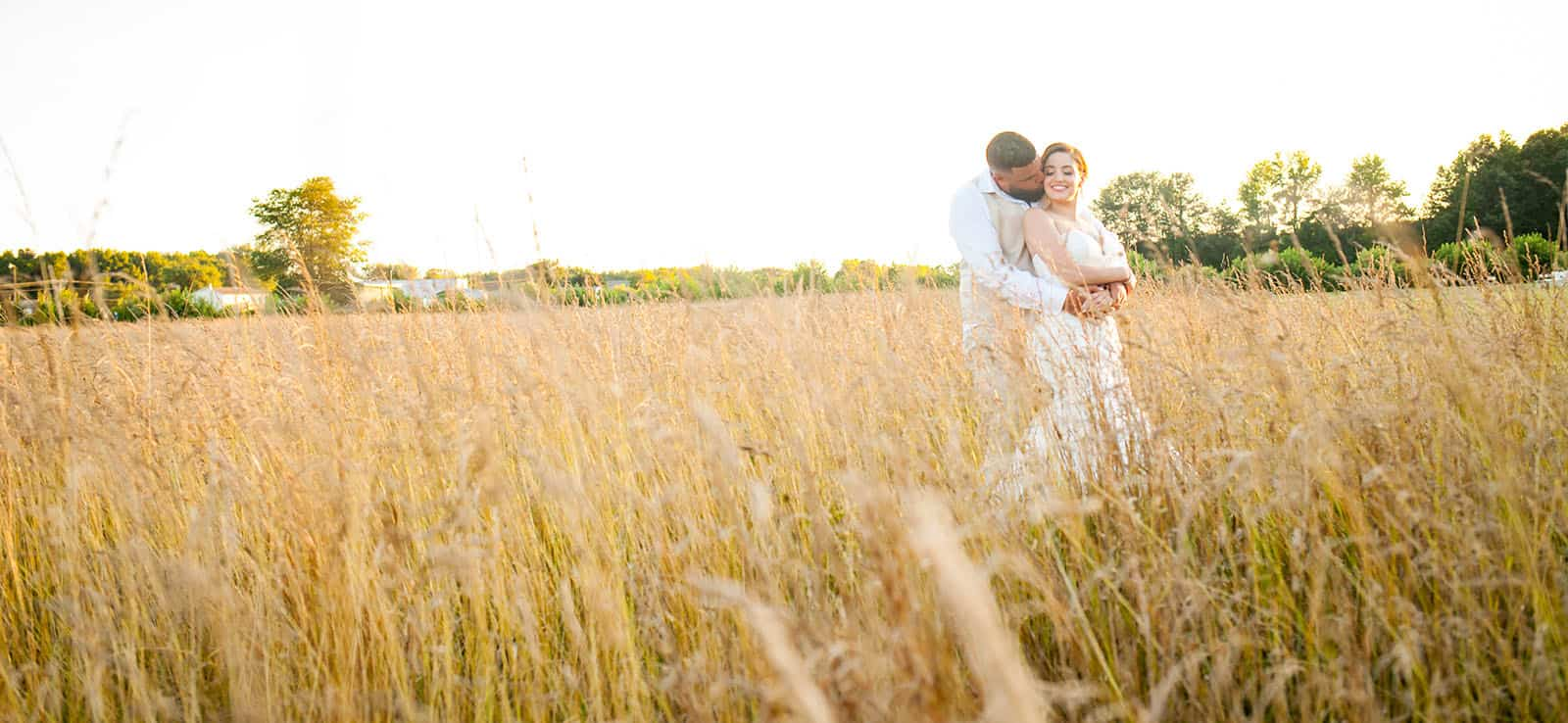 groom kisses bride on the neck from behind in tall grass field