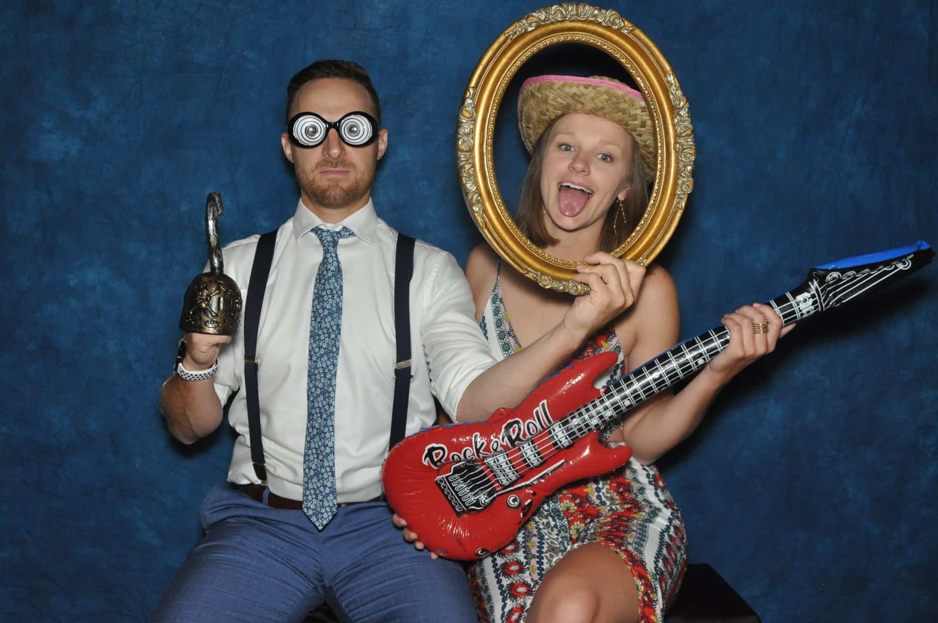 couple poses for photo booth with frame and guitar props