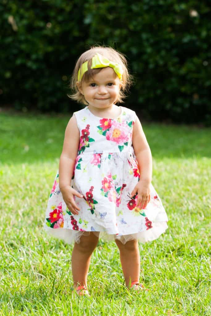 young girl in flower dress and yellow headband smiling