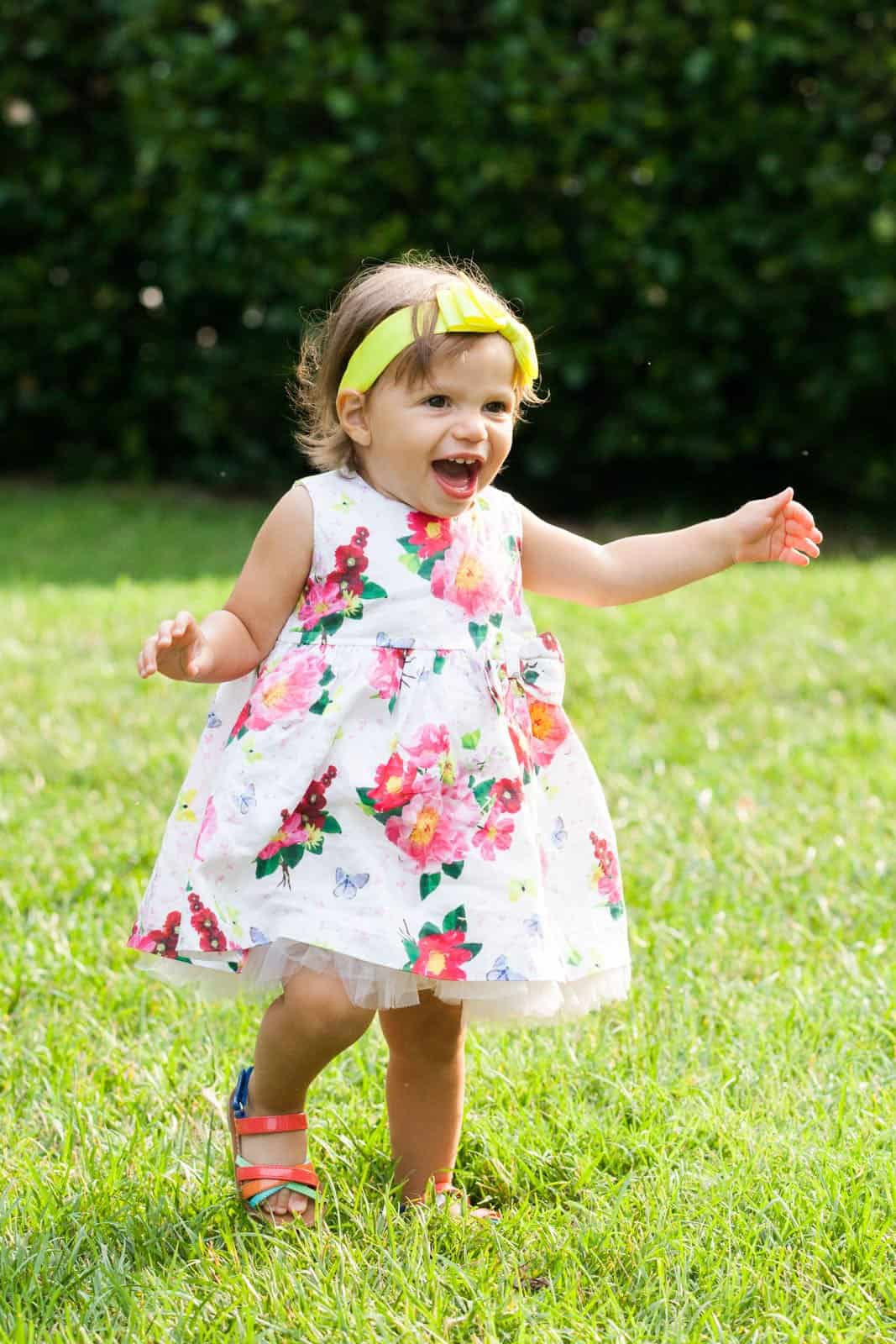 young girl in flower dress and yellow headband