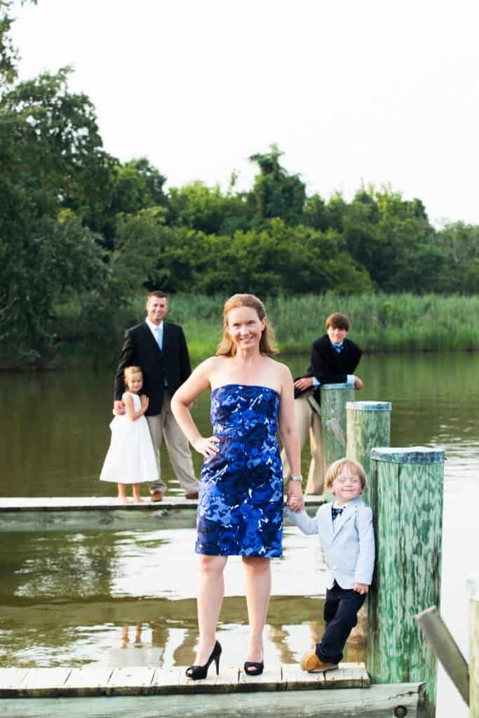 mom with son on a dock with dad behind