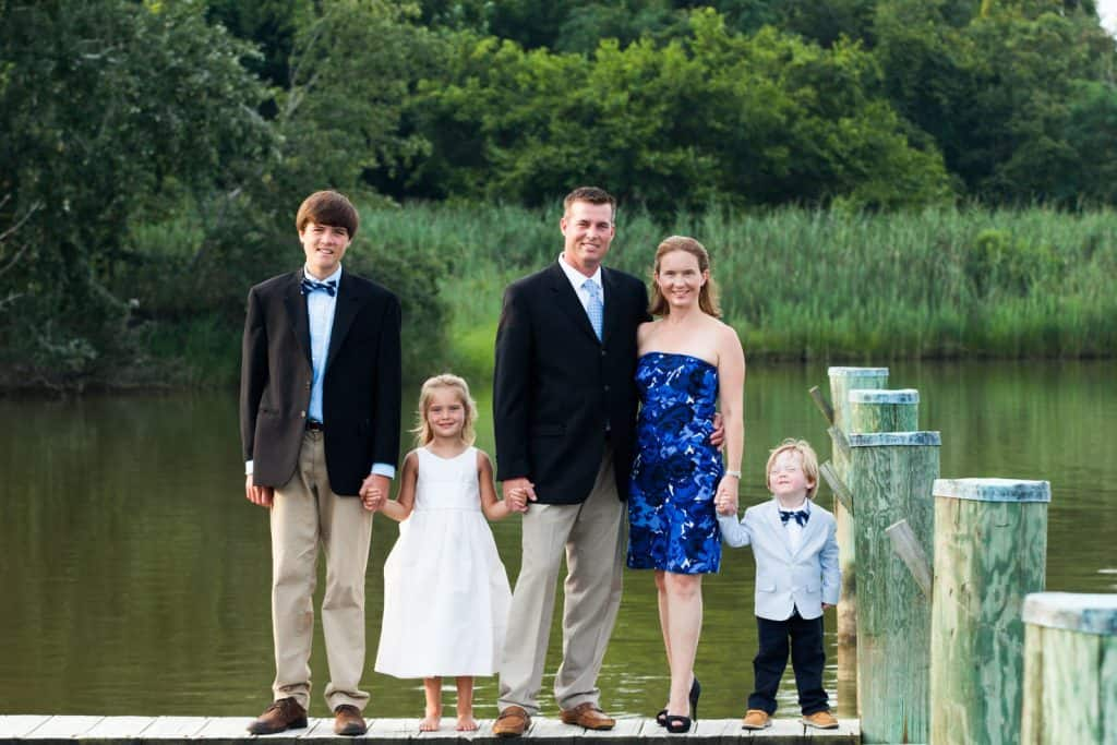 family standing on a dock holding hands