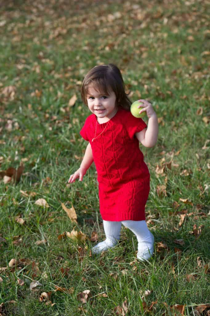 young girl in red dress holding a tennis ball