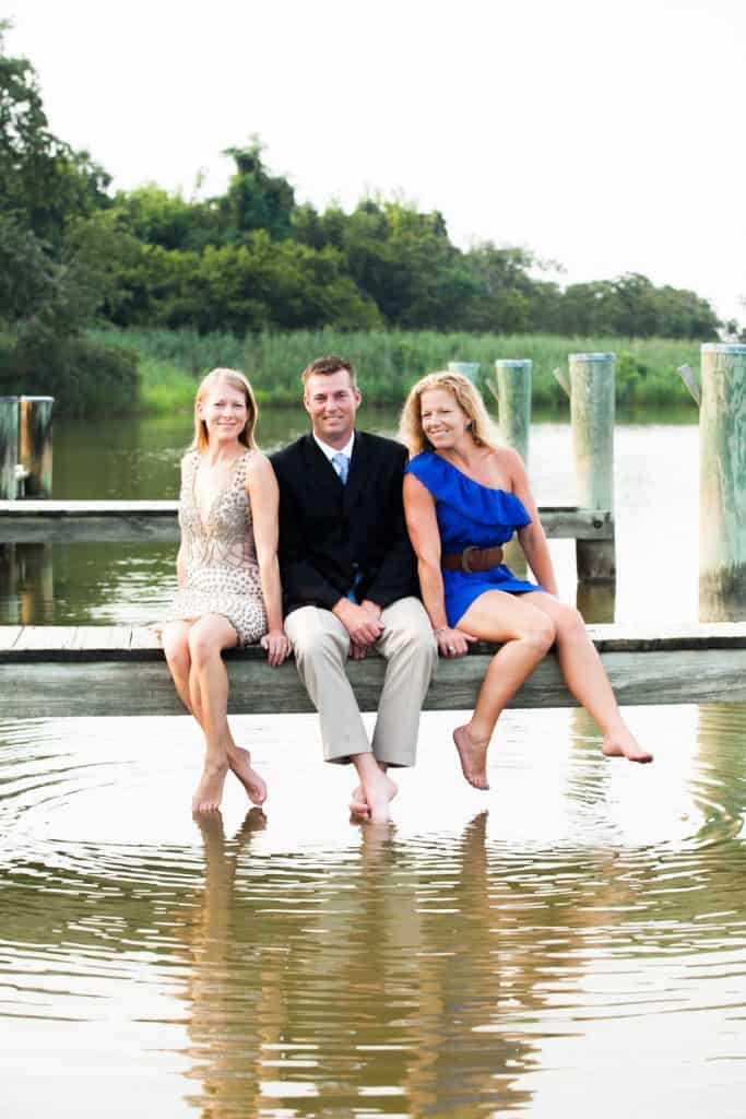 brother and sisters sitting on a dock with bare feet