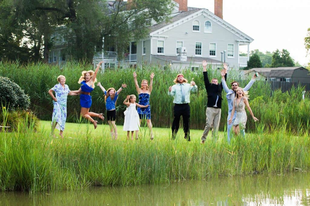 family jumping in the air at a lake