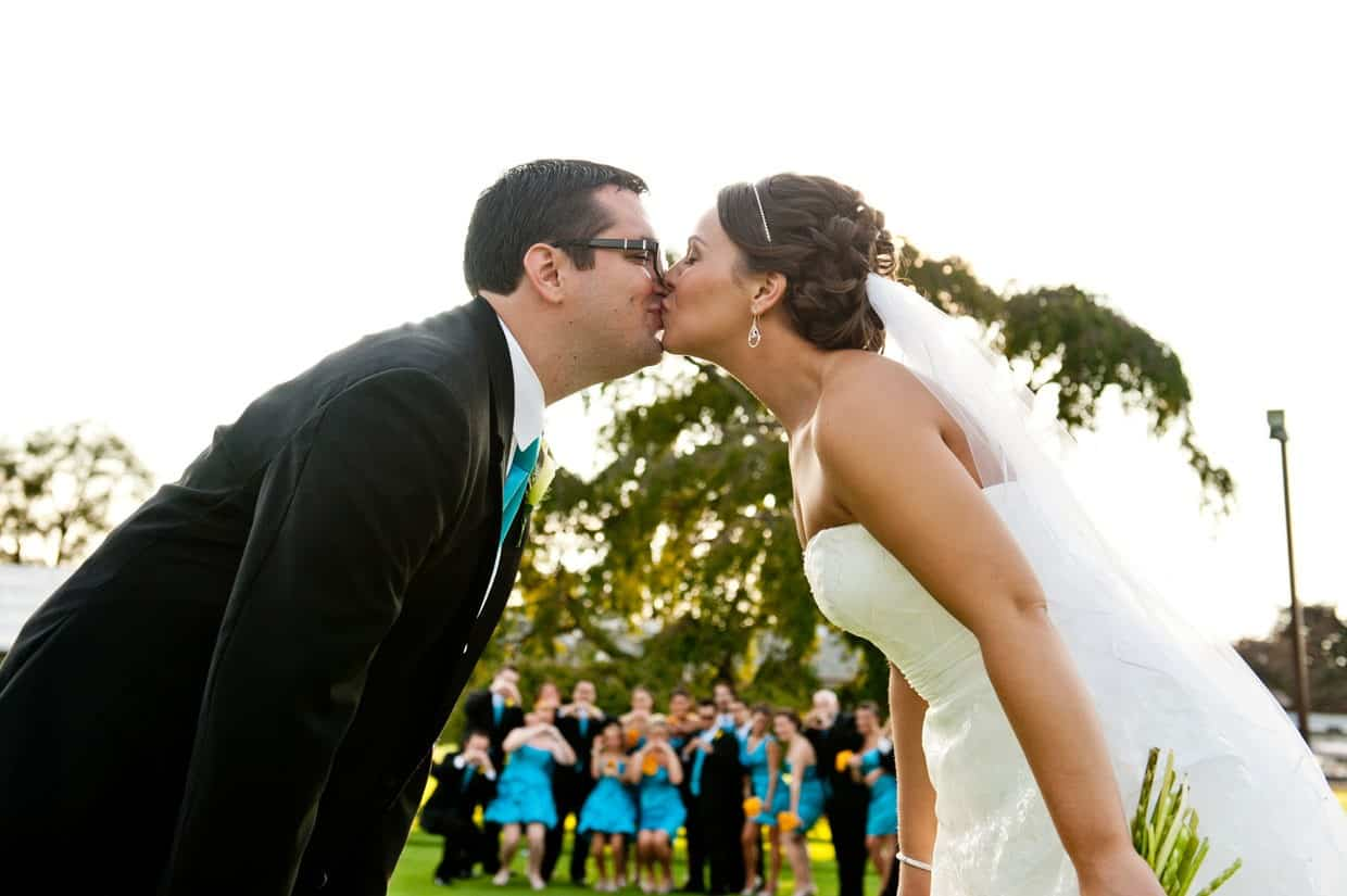 Kissing with bridal party behind at Penn Oaks Country Club
